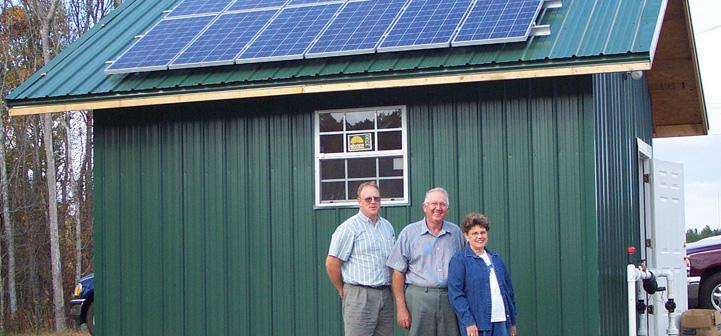 Family standing next to a solar installation on their shed.